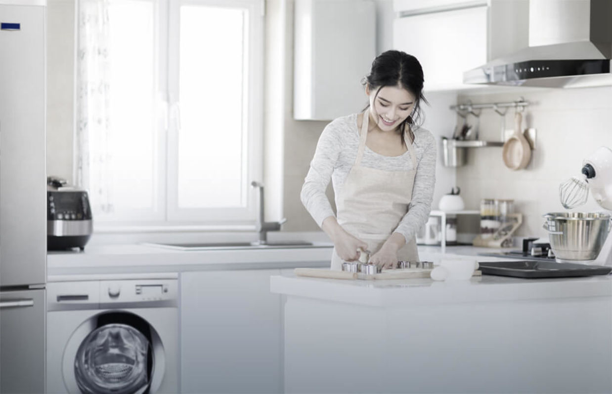 Smiling woman cooking in a modern kitchen.