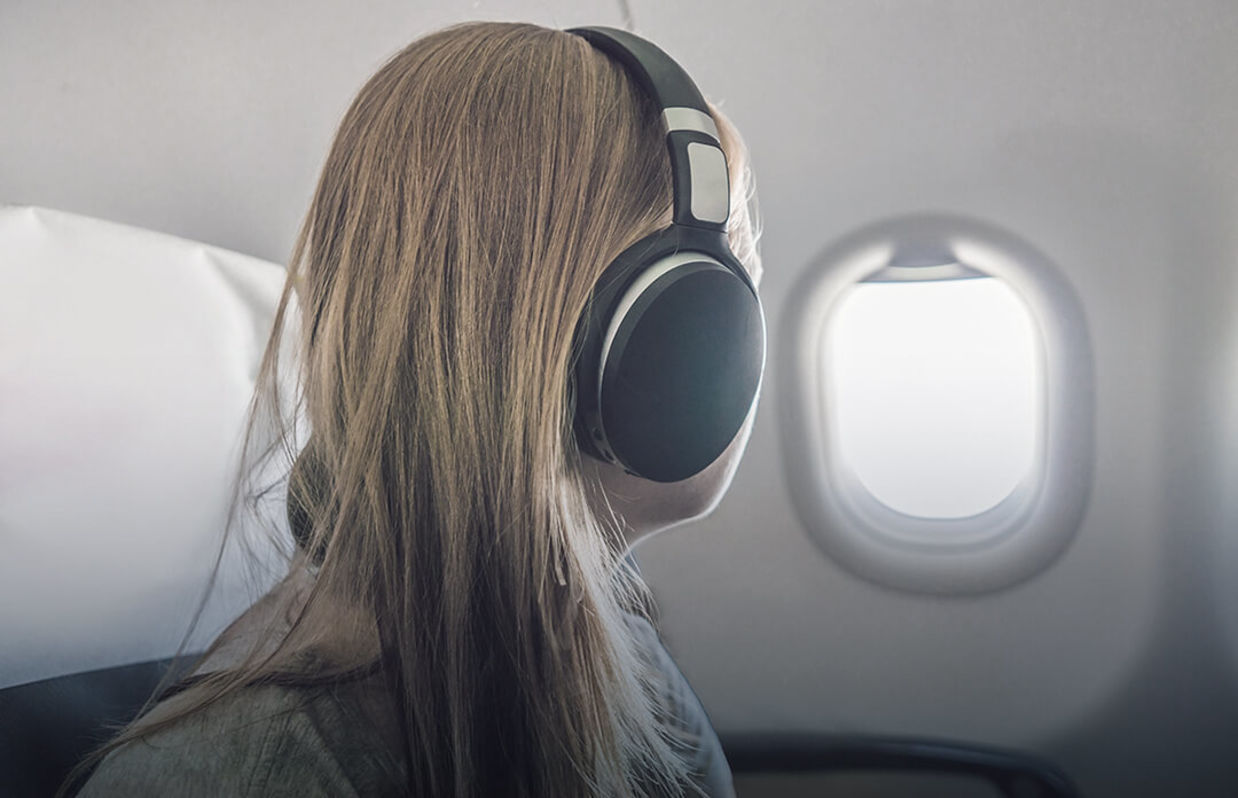 Passenger in airplane using headphones. Woman in plane cabin listening to music on headphones.