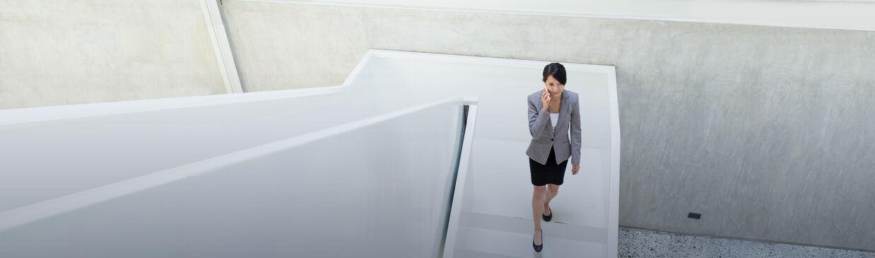 Geschäftsfrau, die in einem hallenden Raum mit dem Mobiltelefon spricht.