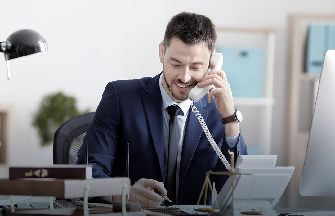 Young business man with VoIP telephone at his office desk